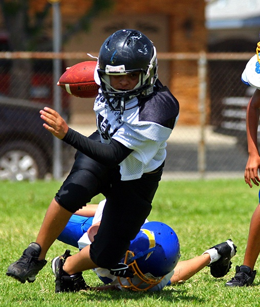 Teen playing football with athletic mouthguard