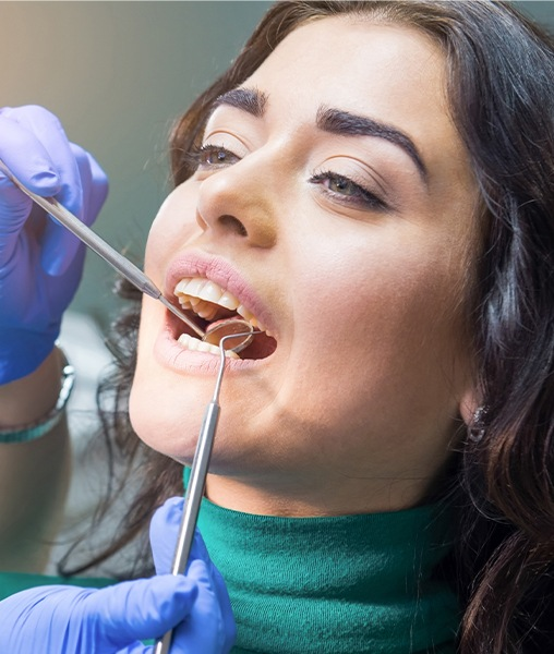 Woman receiving dental exam to prevent the need for emergency dentistry