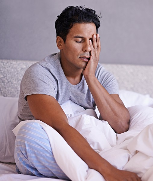 Frustrated man in need of sleep apnea treatment waking feeling unrested
